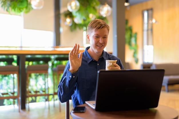 コーヒーショップでコーヒービデオ通話で幸せな若いハンサムな実業家