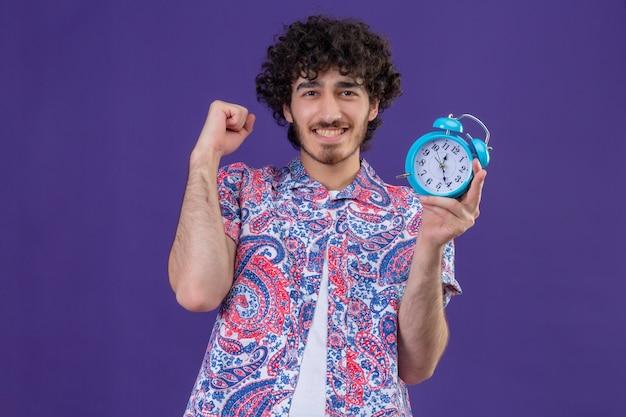 Счастливый молодой красивый фигурный путешественник мужчина держит будильник с поднятым кулаком на изолированном фиолетовом пространстве с копией пространства