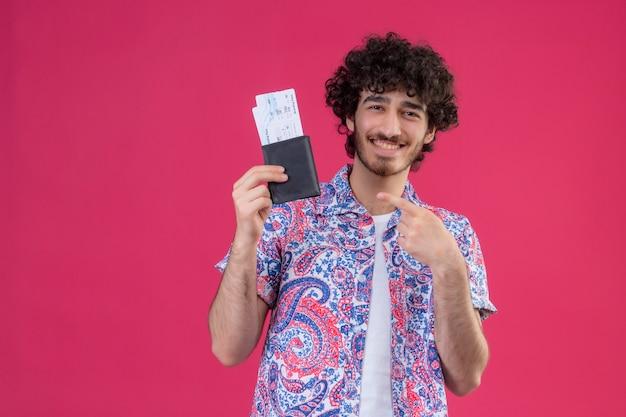 飛行機のチケットと財布を示し、コピースペースと孤立したピンクのスペースでそれらを指している幸せな若いハンサムな巻き毛の旅行者の男