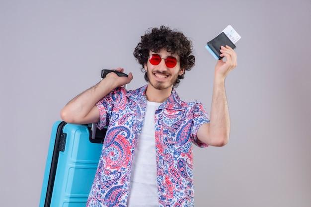 コピースペースと隔離された白いスペースにスーツケースと財布と飛行機のチケットを保持しているサングラスを身に着けている幸せな若いハンサムな巻き毛の旅行者の男