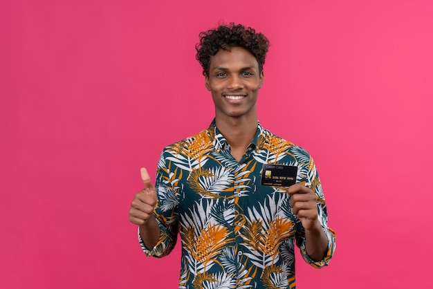 Happy young handsome dark-skinned man with curly hair in leaves printed shirt  while holding and showing credit card with posing with thumbs up sign