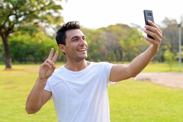 Счастливый молодой красавец латиноамериканского происхождения, делающий селфи с жестом мира
