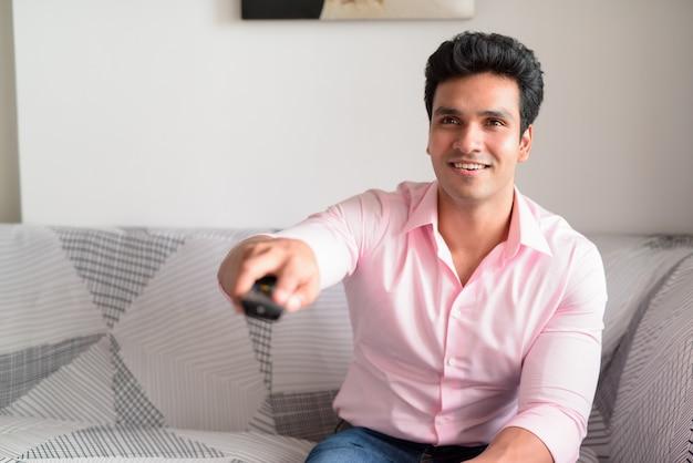 Счастливый молодой красивый индийский бизнесмен смотрит телевизор дома