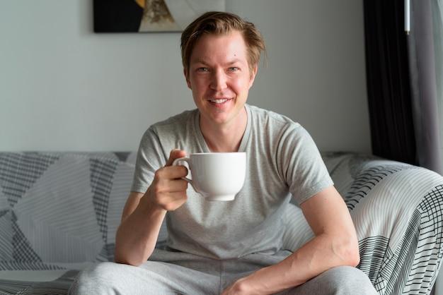 自宅の居間でコーヒーを飲む幸せな若いハンサムな男
