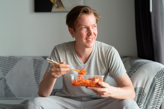 キムチを食べて、自宅のリビングルームで考える幸せな若いハンサムな男