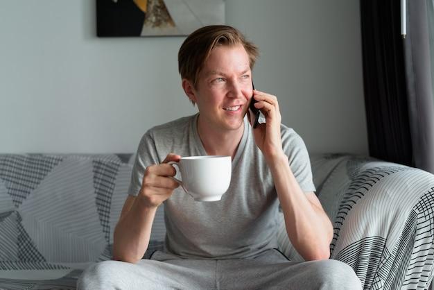 コーヒーを持って、家で電話で話している幸せな若いハンサムな男