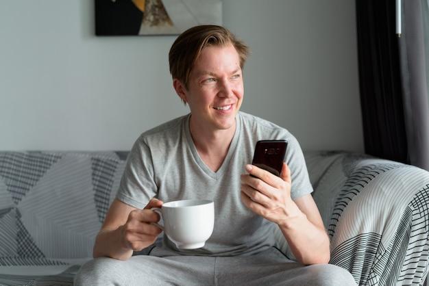 家で考えながらコーヒーカップと電話を保持している幸せな若いハンサムな男