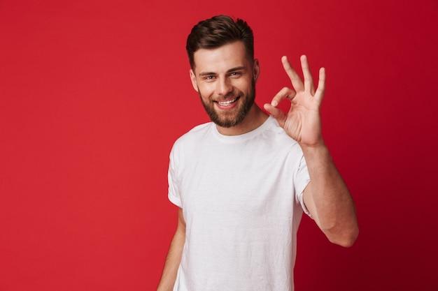 Счастливый молодой красивый человек показывая нормальный жест.