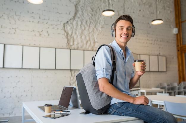Счастливый молодой красавец, сидящий на столе в наушниках с рюкзаком в коворкинг-офисе, пьет кофе