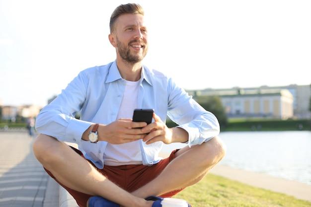 屋外のベンチに座って、スマートフォンを使用して幸せな若いハンサムな男。