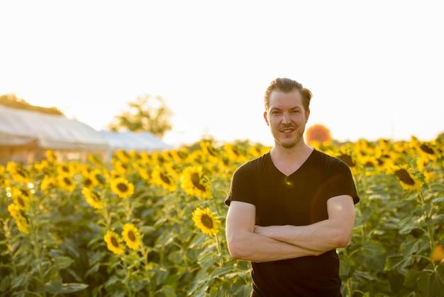 Счастливый молодой красавец улыбается со скрещенными руками в поле