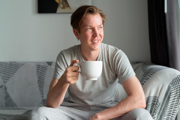 自宅のリビングルームでコーヒーを飲みながら考えている幸せな若いハンサムな男