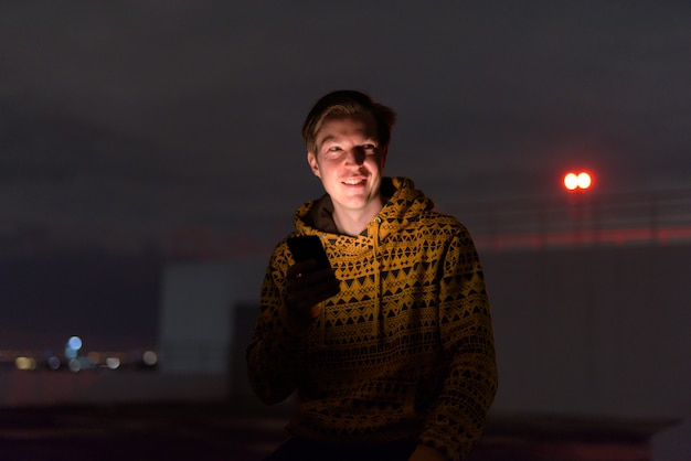 Happy young handsome man thinking while using phone at rooftop of the building during stormy weather at night