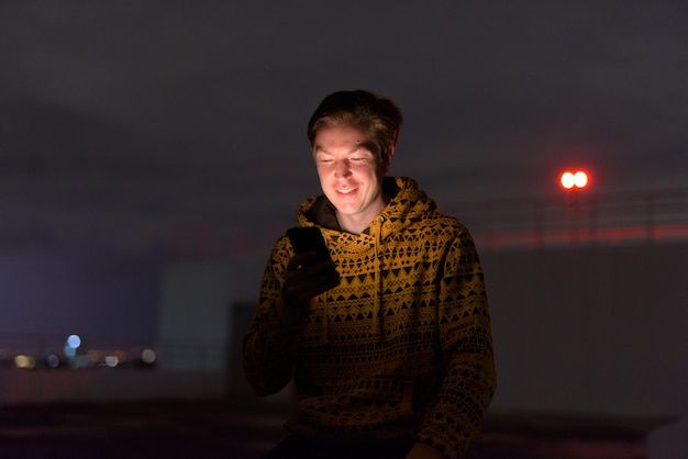 Happy young handsome man using phone at rooftop of the building during stormy weather at night