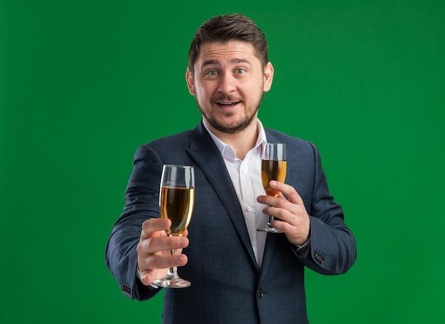 녹색 벽 위에 서있는 얼굴에 미소로 발렌타인 데이를 축하하려고 샴페인 잔을 들고 양복을 입고 행복 젊은 잘 생긴 남자