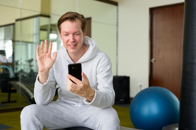 Счастливый молодой красавец с толстовкой по видеосвязи и сидя в тренажерном зале