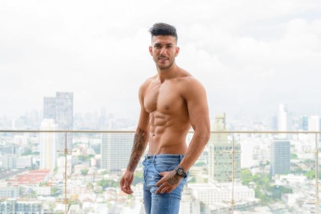 Счастливый молодой красивый мускулистый персидский мужчина без рубашки с видом на город