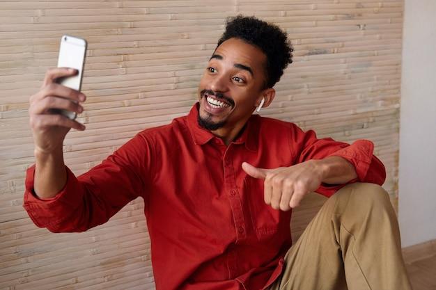 Счастливый молодой красавец с короткими волосами бородатый брюнетка, счастливо улыбаясь во время видеозвонка со своего мобильного телефона, сидя на бежевом интерьере в повседневной одежде