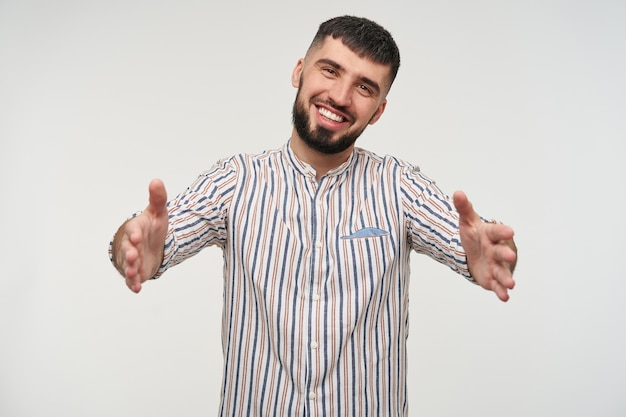 Felice giovane bel ragazzo barbuto dai capelli corti bruna in camicia a righe che guarda allegramente con un ampio sorriso, in piedi sopra il muro bianco con le braccia aperte