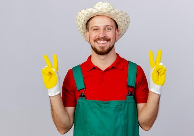 Счастливый молодой красивый славянский садовник в униформе в садовых перчатках и шляпе делает знак мира на белой стене