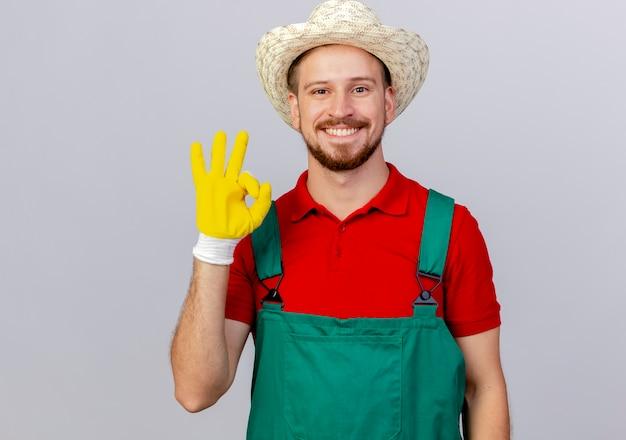 Felice giovane giardiniere slavo bello in uniforme che indossa guanti da giardinaggio e cappello facendo segno ok isolato sulla parete bianca con lo spazio della copia