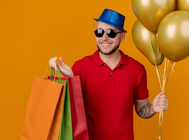 オレンジ色の背景に分離された風船と紙袋を保持しているサングラスとパーティー帽子を身に着けている幸せな若いハンサムなスラブパーティー男