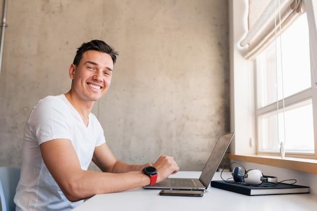 ラップトップに取り組んでいるテーブルに座っているカジュアルな服装で幸せな若いハンサムな笑みを浮かべて男