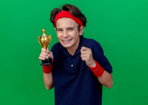 Happy young handsome sporty boy wearing headband and wristbands with dental braces holding winner cup clenching fist looking at front isolated on green wall