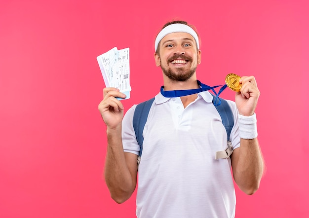 Happy young handsome sporty man wearing headband and wristbands and back bag with medal around neck holding medal and airplane tickets isolated on pink wall with copy space