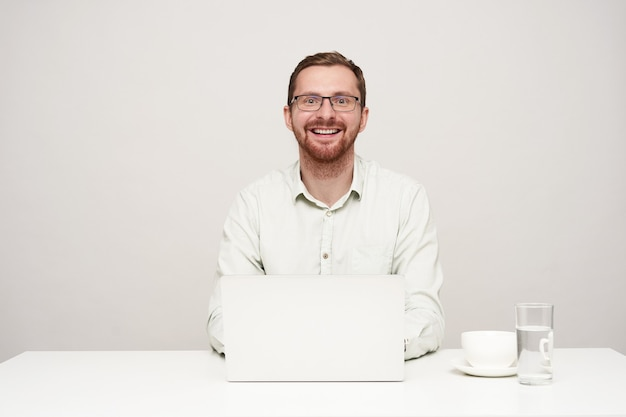Happy young handsome unshaved male in eyewear looking gladly at camera with wide smile while working with his laptop over white background, being in high spirit