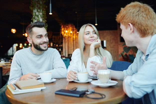 Happy young heterosexual couple chatting to their friend by cup of cappuccino while relaxing in cafe after work or college