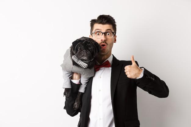 Счастливый молодой хипстер в костюме и очках, показывая большой палец вверх, держа милую черную собаку на плече, любит его мопса, стоящего над белой.