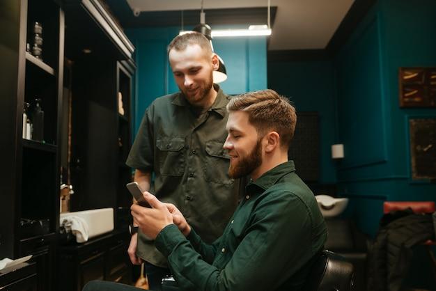 Счастливый молодой битник человек стрижка парикмахером, сидя в кресле.