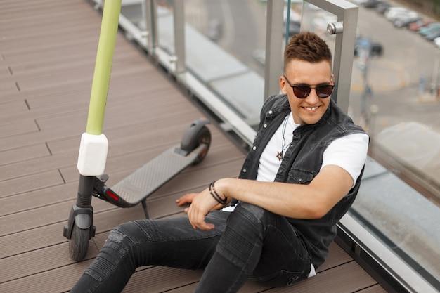 신발에 청바지에 선글라스에 유행 데님 조끼에 미소로 행복 한 젊은 hipster 남자는 도시에서 유리 벽 근처에 앉아 이완.