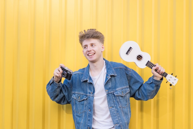 Happy young hipster stands on a yellow wall with ukulele and a retro camera in his hands