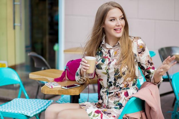 幸せな若い流行に敏感なスタイリッシュな女性のカフェ春夏のファッショントレンドに座って、コーヒーを飲む
