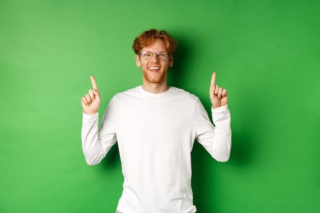 빨간 머리, 안경을 쓰고, 손가락을 가리키고, 승진을 보여주는, 카메라에 미소를 짓고, 녹색 배경 위에 서있는 행복 한 젊은 소식통.