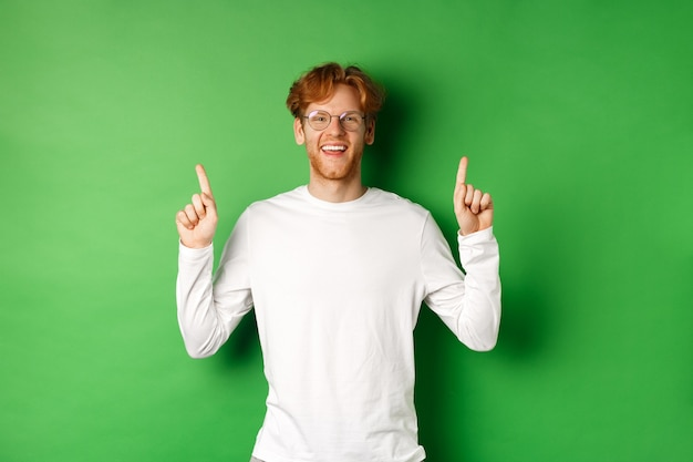 Happy young hipster with red hair, wearing glasses, pointing fingers up and showing promotion, smiling at camera, standing over green background.