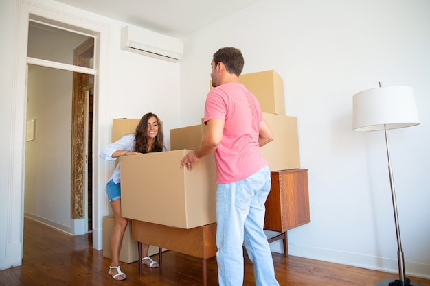 Happy young hispanic couple moving into new flat, carrying carton boxes and furniture