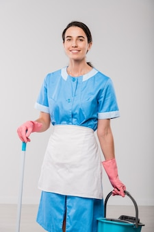 Happy young hotel room cleaning staff in uniform and rubber gloves holding bucket and mop while standing in front of camera in isolation