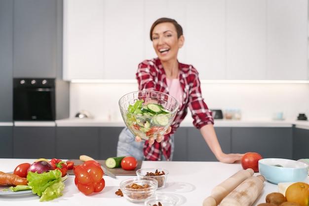 Счастливая молодая домохозяйка держит салат, приготовленный для семейного обеда