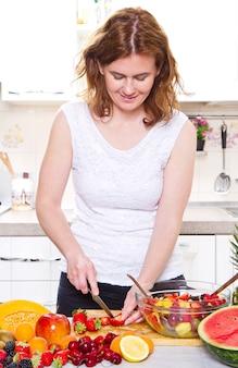 フルーツサラダを作る幸せな若い主婦