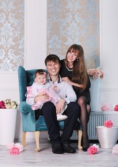 Счастливая молодая идеальная улыбающаяся семья дома, мать, отец и дочь
