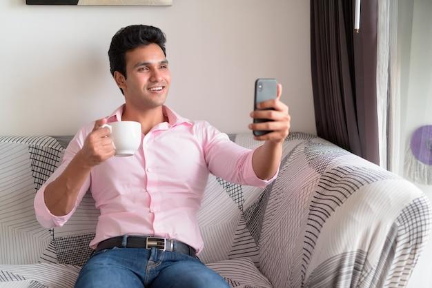 Счастливый молодой индийский бизнесмен, делающий селфи, пить кофе дома