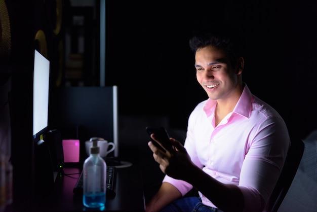 暗闇の中で検疫中に自宅で残業しながら電話を使用して幸せな若いインドのビジネスマン