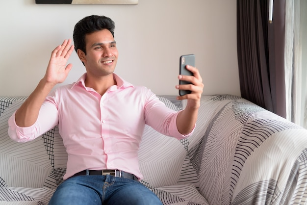 Счастливый молодой индийский бизнесмен видеозвонок с телефоном дома