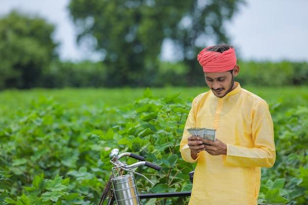 Счастливый молодой индийский фермер считает и показывает деньги