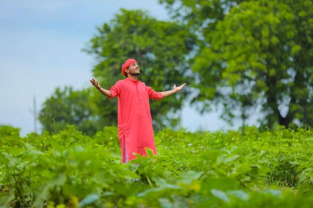 Счастливый молодой индийский фермер, стоящий в зеленом поле баклажанов