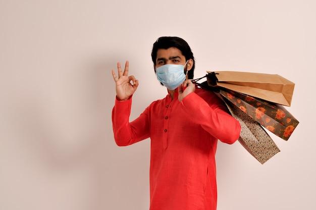 행복 한 젊은 인도 남자 쇼핑 가방과 함께 kurta 마스크를 입고 한과 함께 확인 제스처를 보여주는