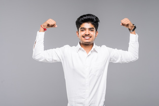 Happy young indian man showing biceps over grey wall